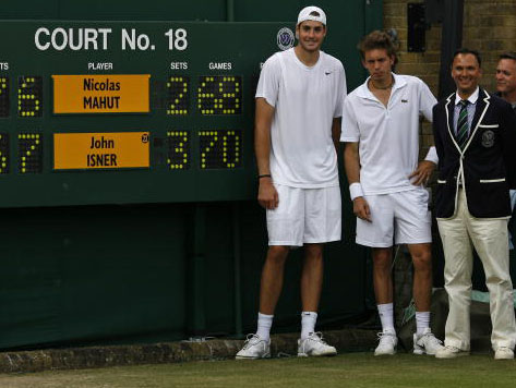 Farce. Niclas Mahut begrudgingly joins John Isner and umpire Mohamed Lahyani by the scoreboard at the end of the longest match in tennis history